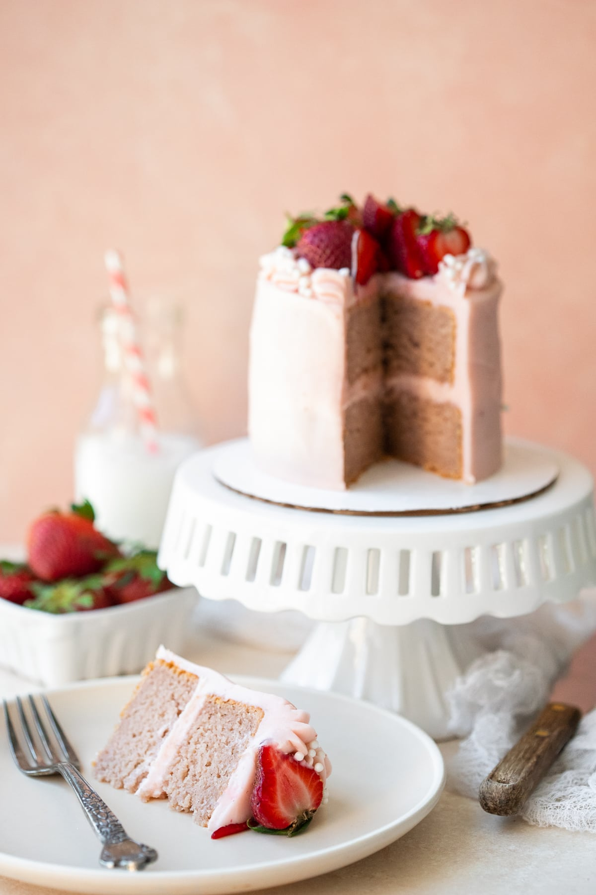 Slice of cake on a plate, with the remainder on a stand in the background, alongside strawberries and a milk bottle.