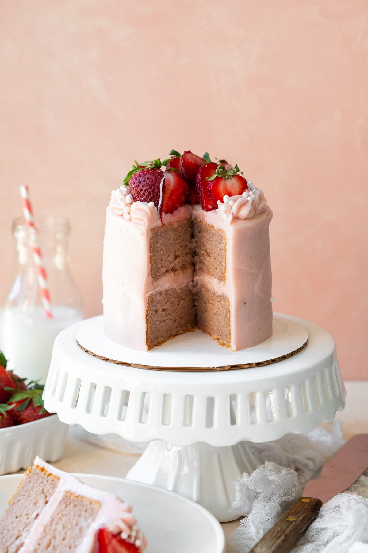 Center cut view of cake on a white stand against a pink backdrop.