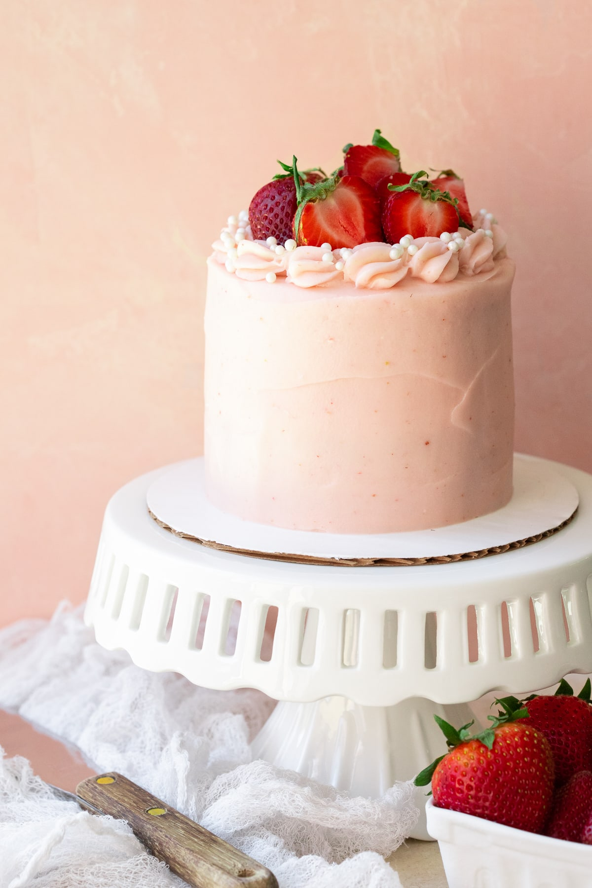 Front-facing view of cake on a white stand, with an icing spatula and extra strawberries to the side.