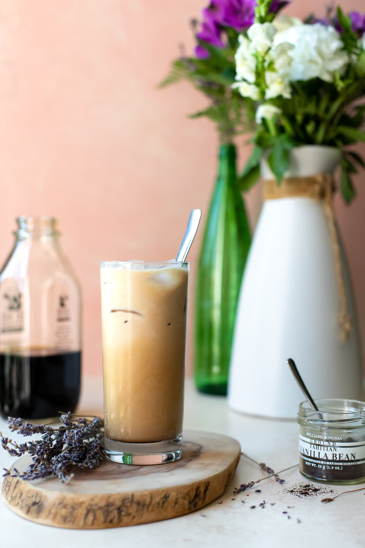 Coffee on a wooden serving board with lavender, vanilla bean, and fresh flowers in the background.