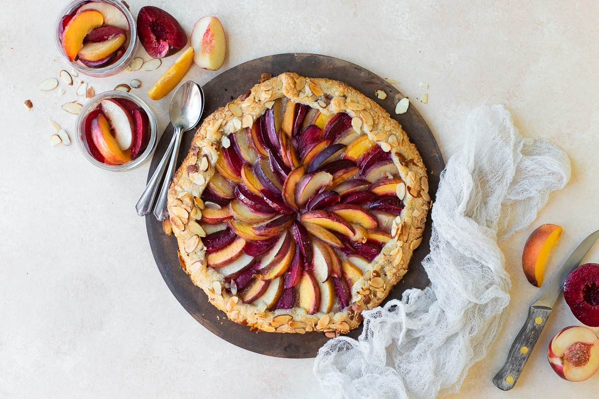 Overhead view of galette on a pizza stone, accented by slices of fruit and a linen.