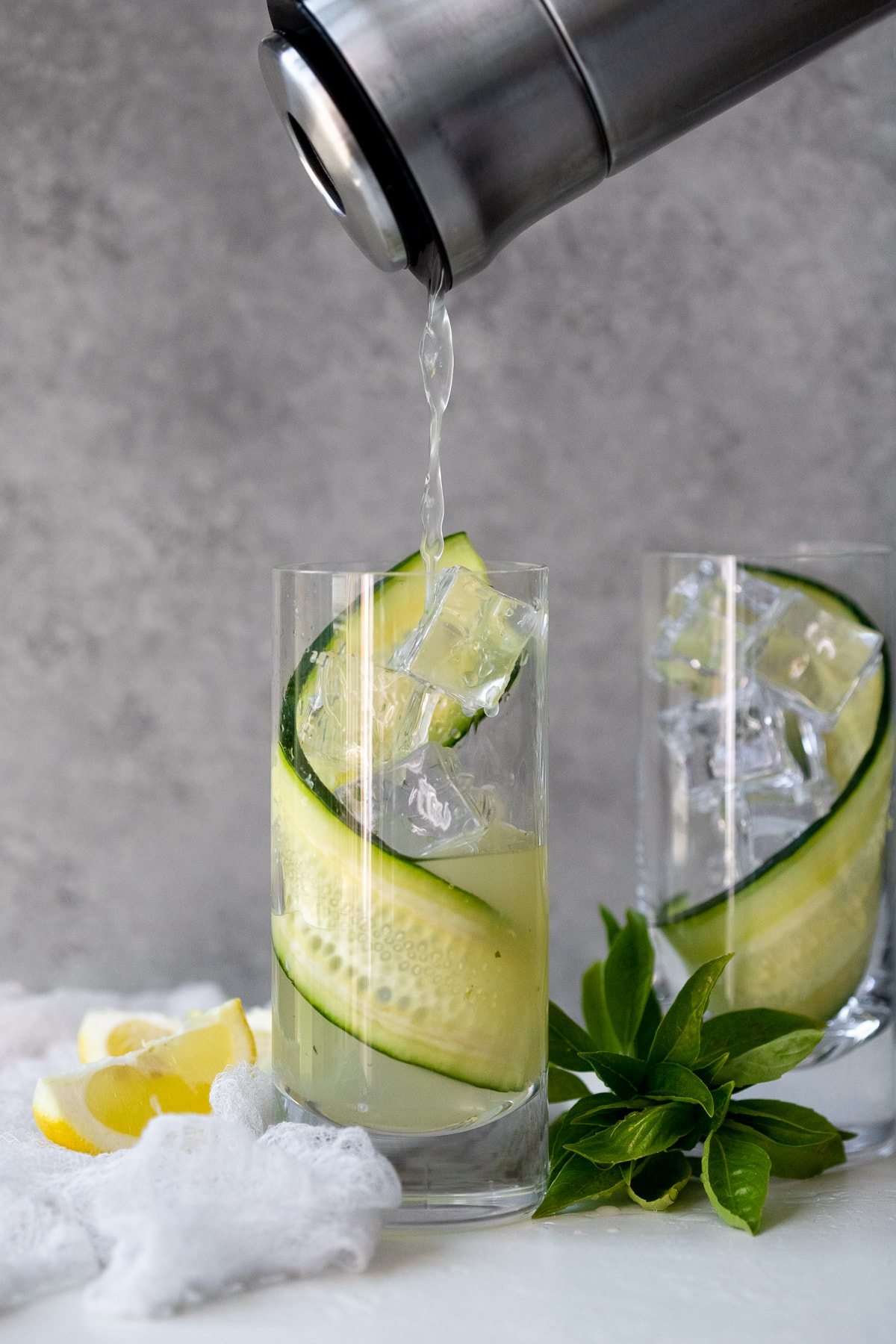 Process shot of liquid being poured out of a cocktail shaker into a highball glass filled with ice and a cucumber ribbon.