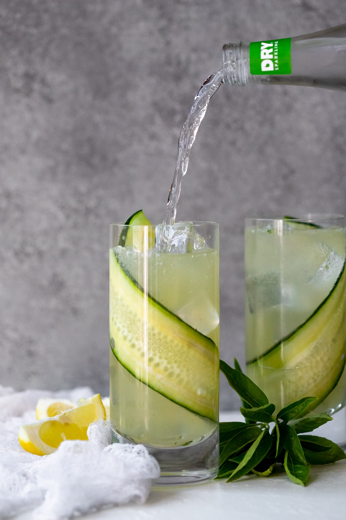 Process shot of cucumber soda being poured into a gin fizz, with lemon wedges and a sprig of basil in the background.