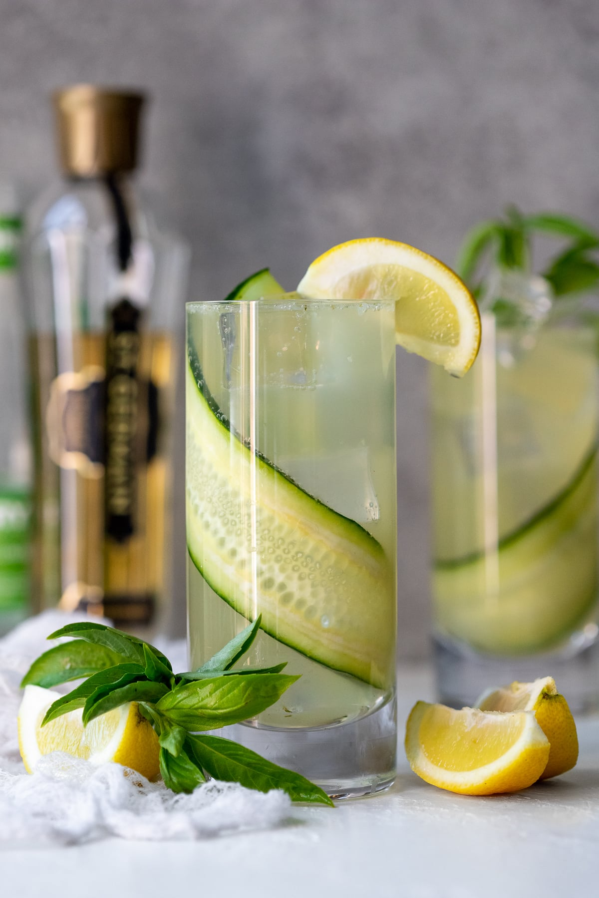 Front view of two gin fizz cocktails with lemon wedges, basil leaves, cucumber soda, and elderflower liqueur in the background.
