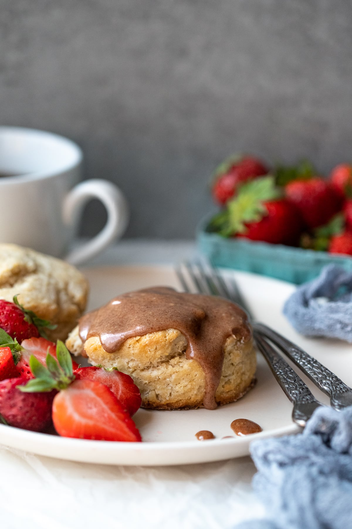 Forward-facing view of two biscuits on a plate, one with cinnamon icing on top, served with fresh berries. A coffee cup and a basket of strawberries are in the background.