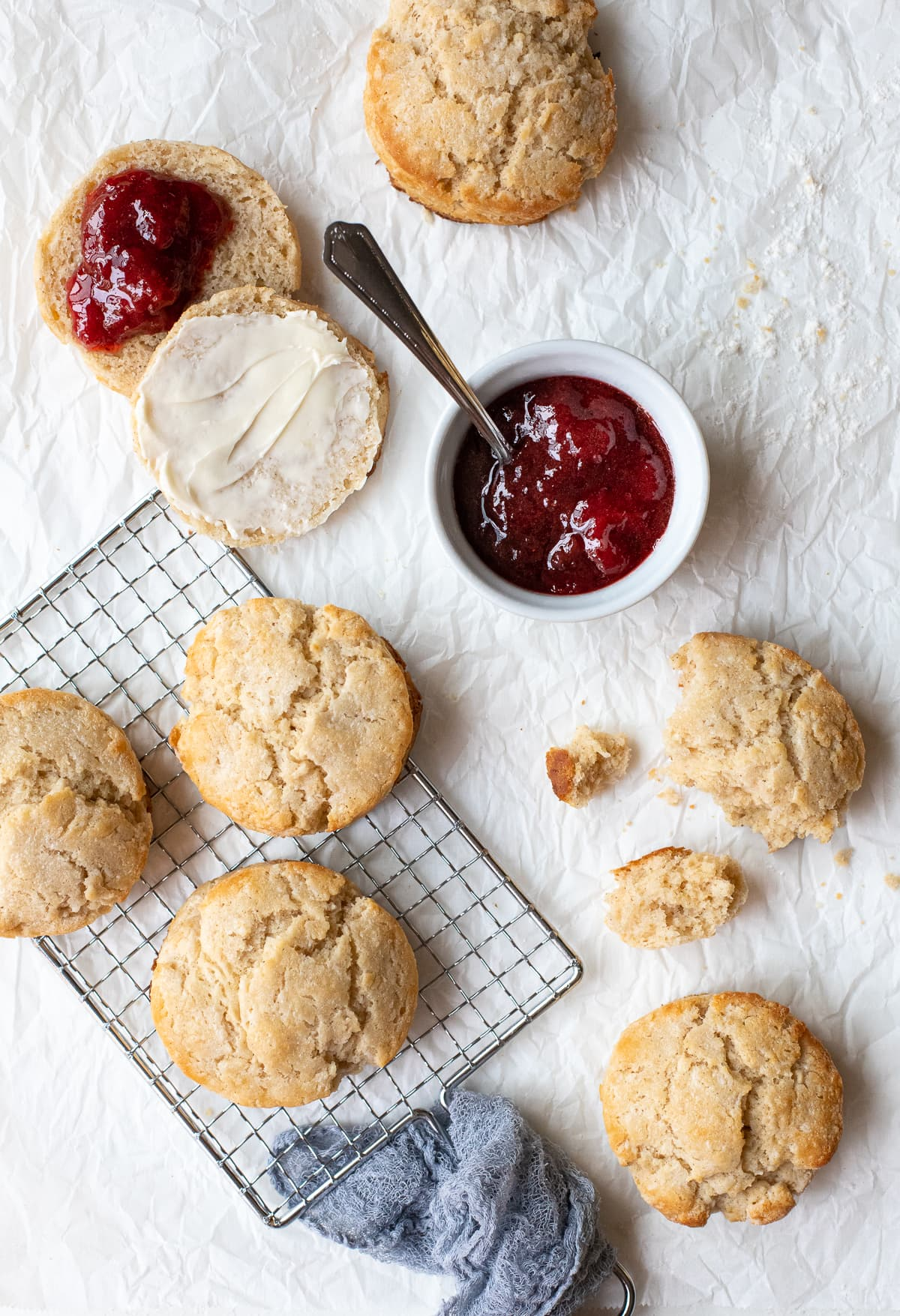 Overhead view of biscuits scattered on a sheet of parchment paper, with butter and jam being used as garnishes.