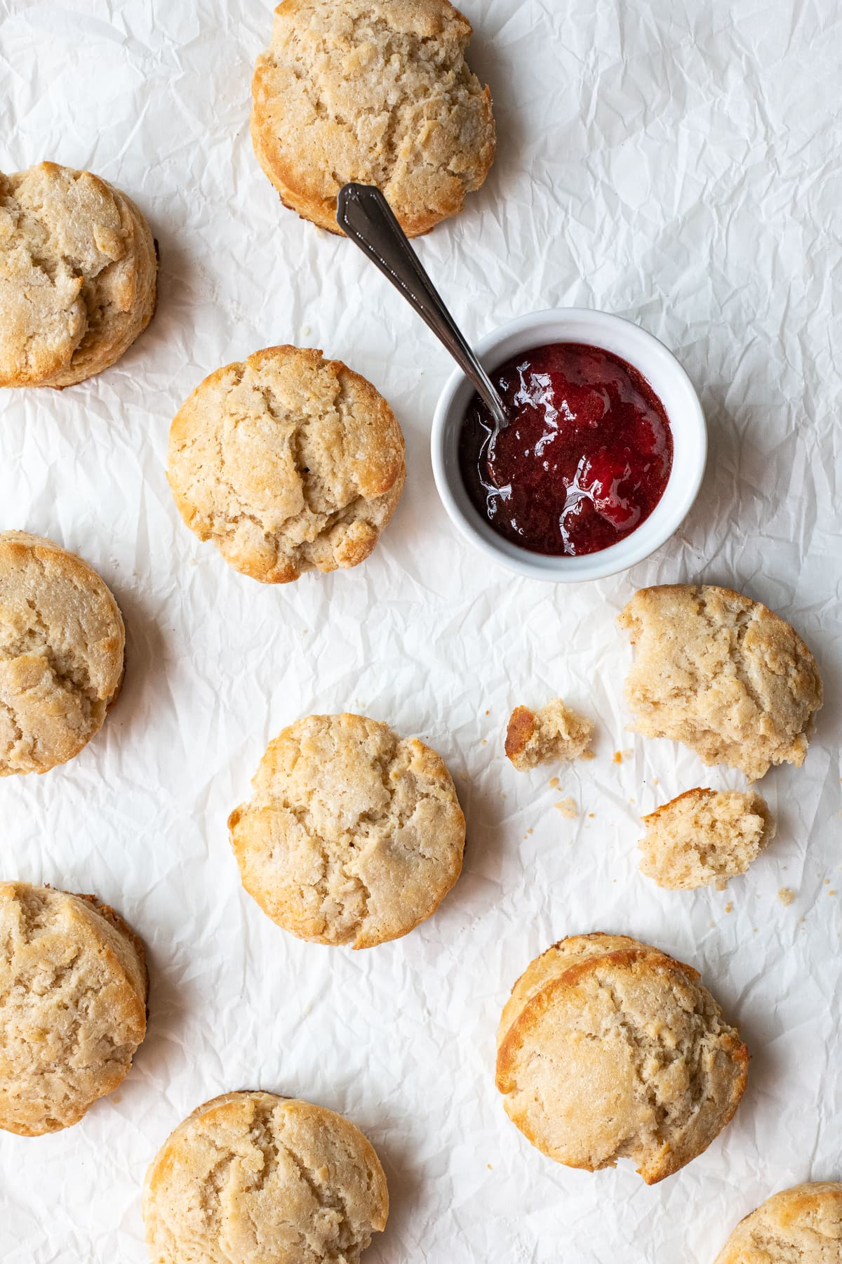 Overhead view of biscuits scattered across a sheet of crumpled parchment paper, alongside a small ramekin full of jam.