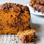 Front-facing view of center cut of pumpkin bread, with slices stacked on a plate in the background.