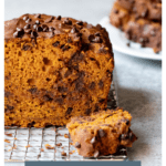 Front-facing view of center cut of pumpkin bread, with slices stacked on a plate in the background. Text overlay reads