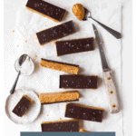 """Overhead view of protein bars scattered on a sheet of parchment paper, alongside a knife and a small bowl of sea salt. Bottom banner reads """"Chocolate Peanut Butter Protein Bars""""."""
