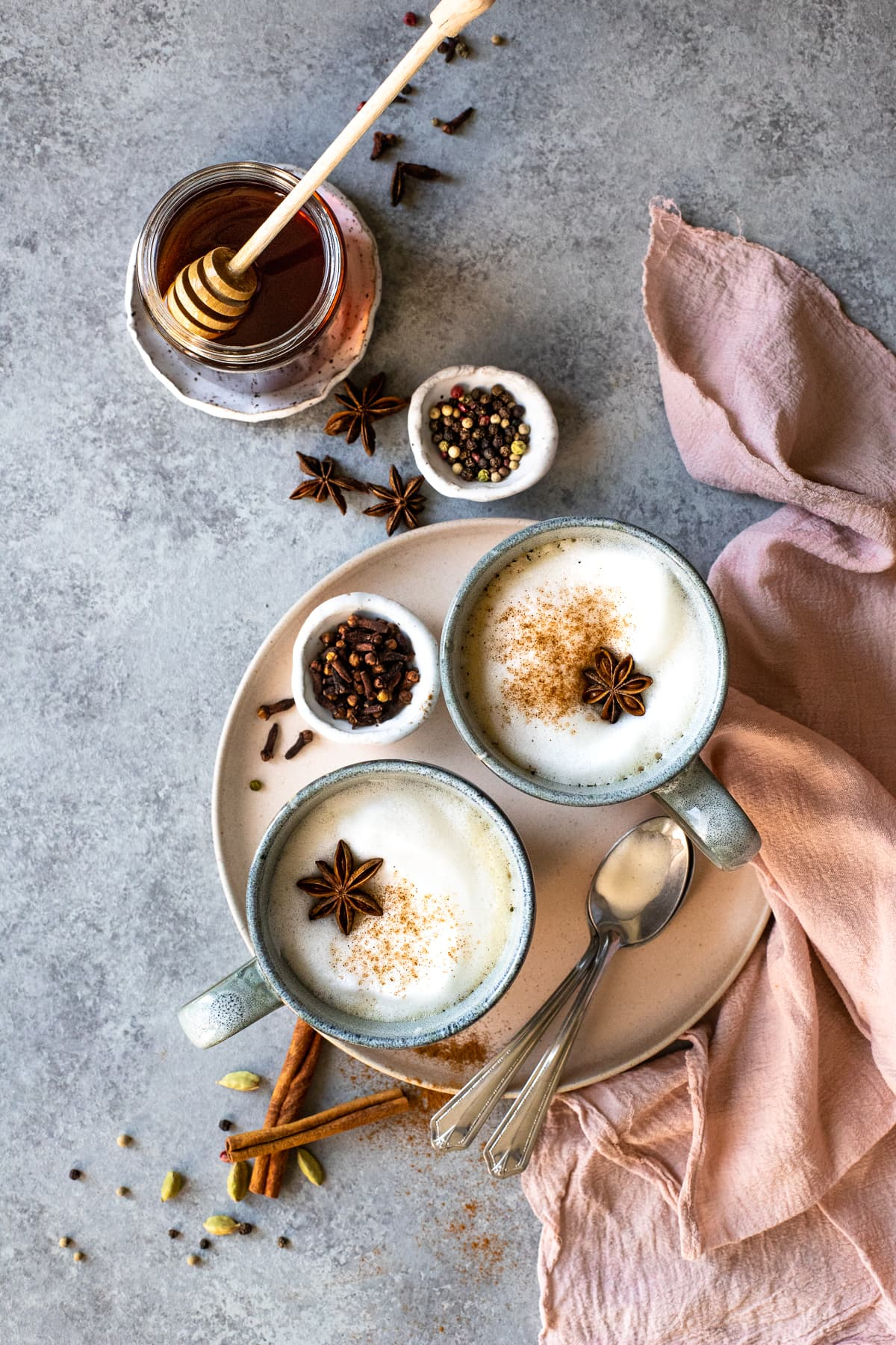 Overhead view of two lattes, surrounded by a jar of honey spices, and a pink linen.