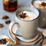 Lattes garnished with star anise and cinnamon, with extra spice and honey in the background. Text overlay reads