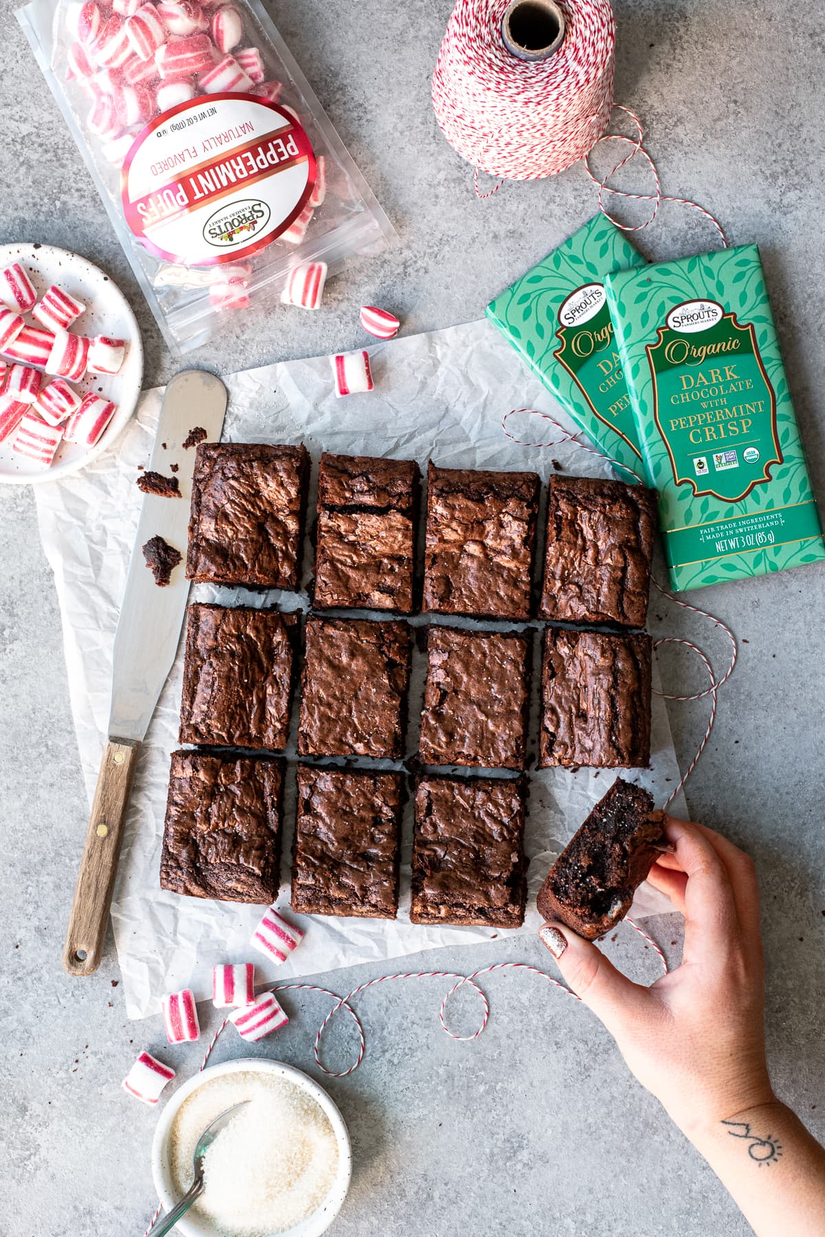 Overhead shot of sliced brownies on a sheet of parchment paper, surrounded by peppermint chocolate and candies. A hand is grabbing one of the brownies.
