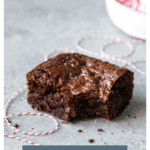 Angled view of a brownie with a bite taken out and text that reads
