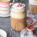 Mocha in a mason jar topped with whipped cream, with candy canes and white chocolate syrup in the background.