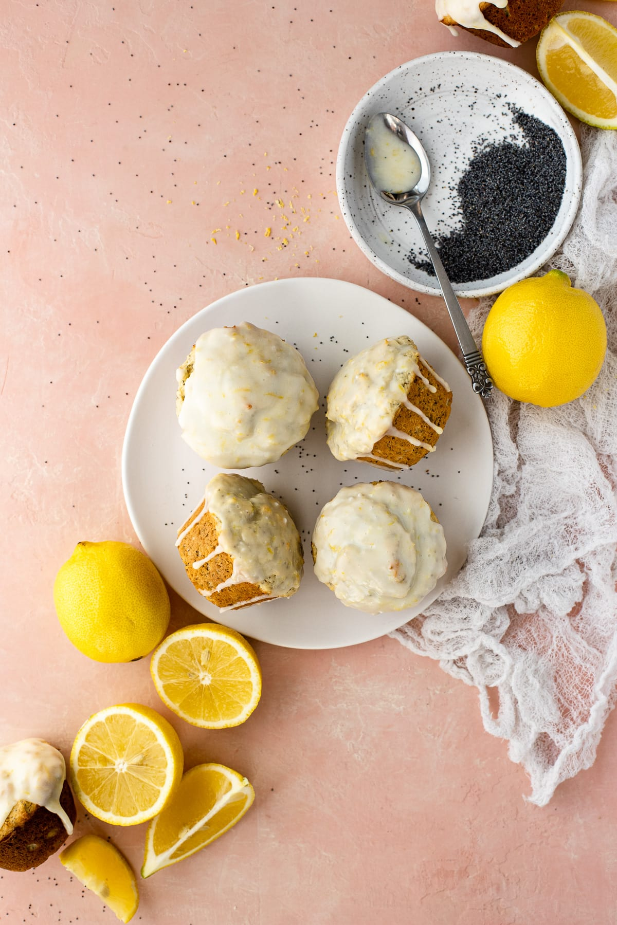 Overhead view of four muffins on a plate, surrounded by fresh lemons and poppy seeds.