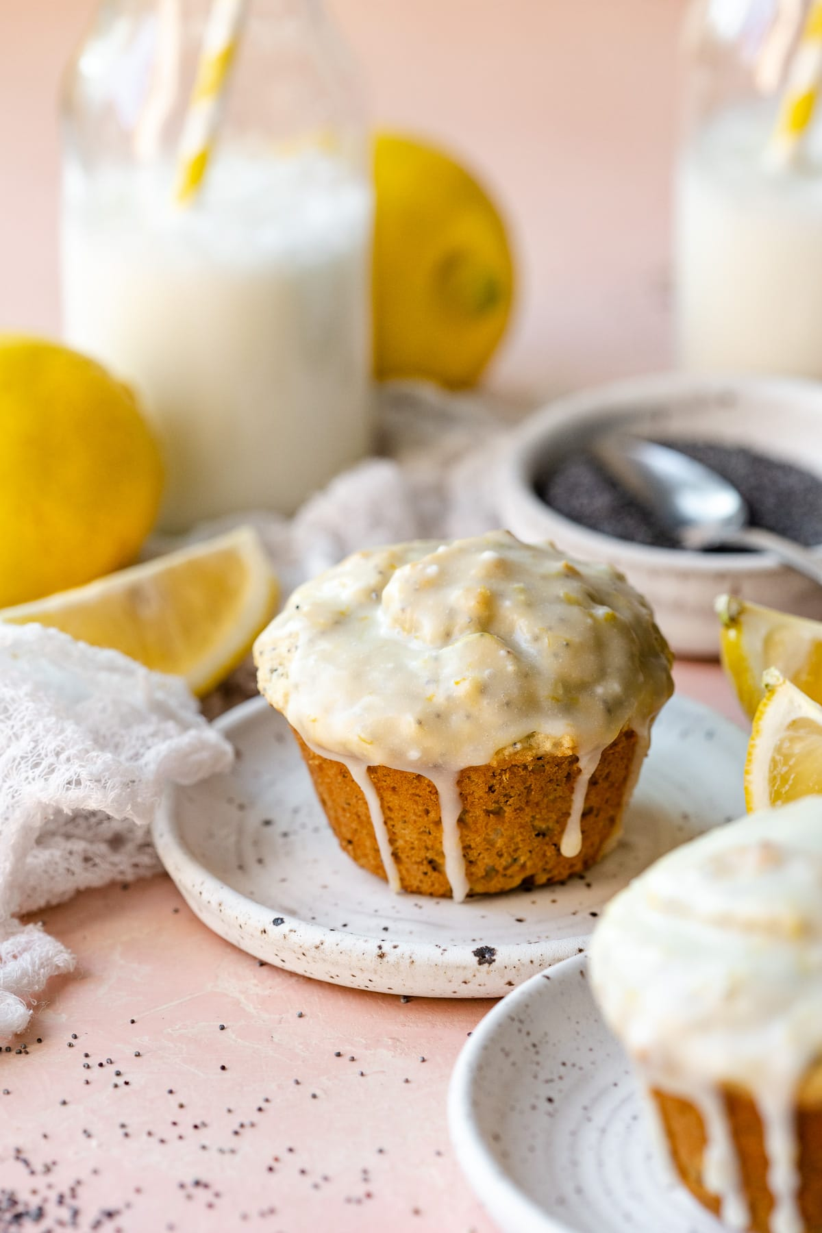 A muffin on a plate, with lemon slices, poppy seeds, and two bottles of milk in the background.