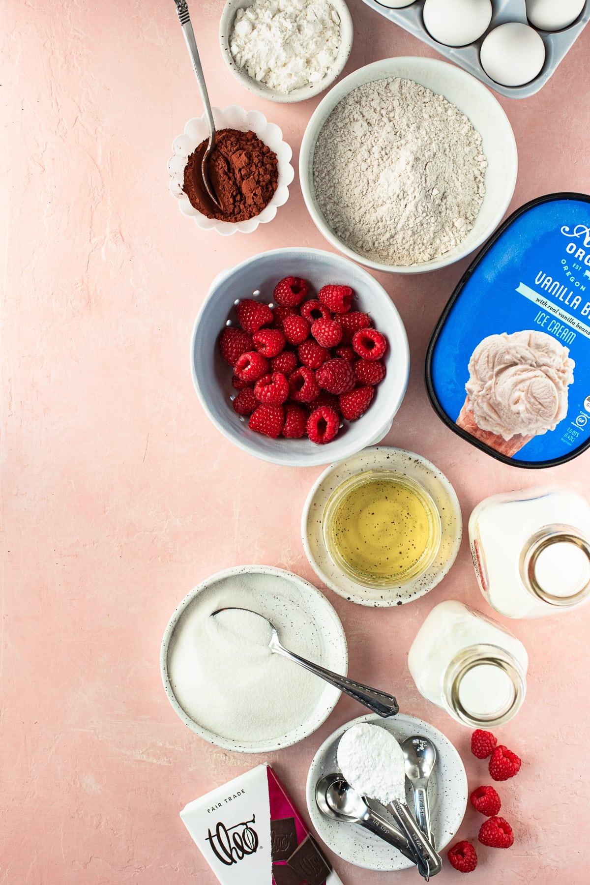 Overhead shot of recipe ingredients including cocoa powder, eggs, flour, cornstarch, raspberries, ice cream, oil, buttermilk, heavy cream, granulated sugar, dark chocolate, and powdered sugar.