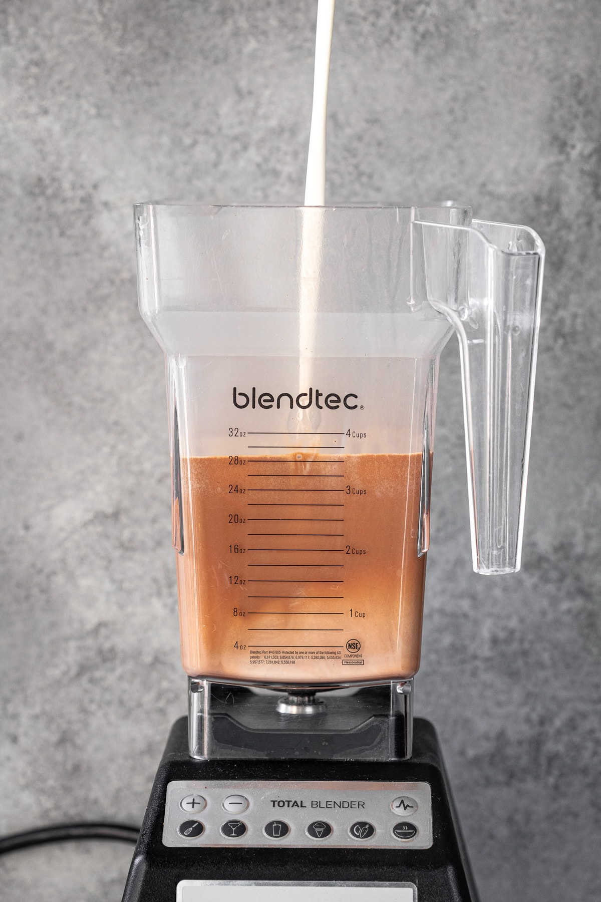 Process shot of cream being poured into a blender.