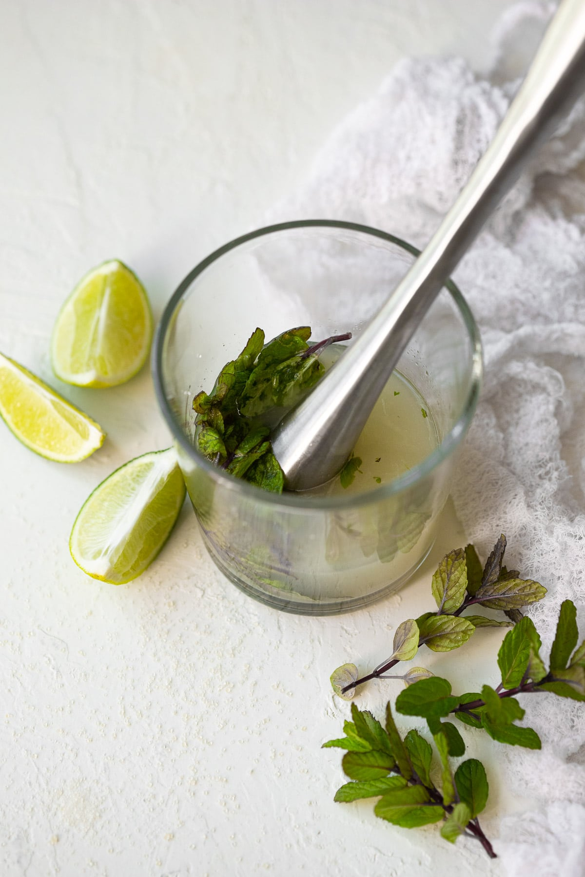 Fresh mint muddled with lime in a small glass.