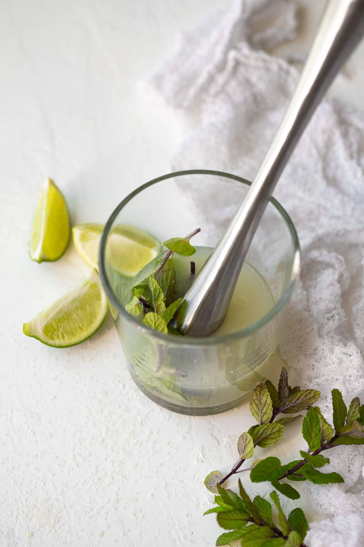 Mint and lime juice combined in a small glass, ready to be muddled.