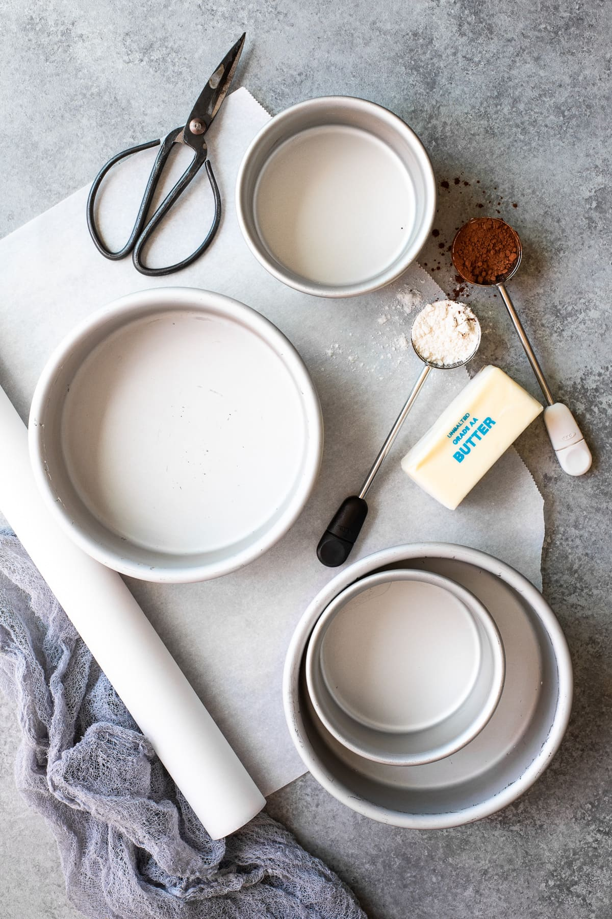 Overhead view of tools need to properly prepare and line a cake pan.