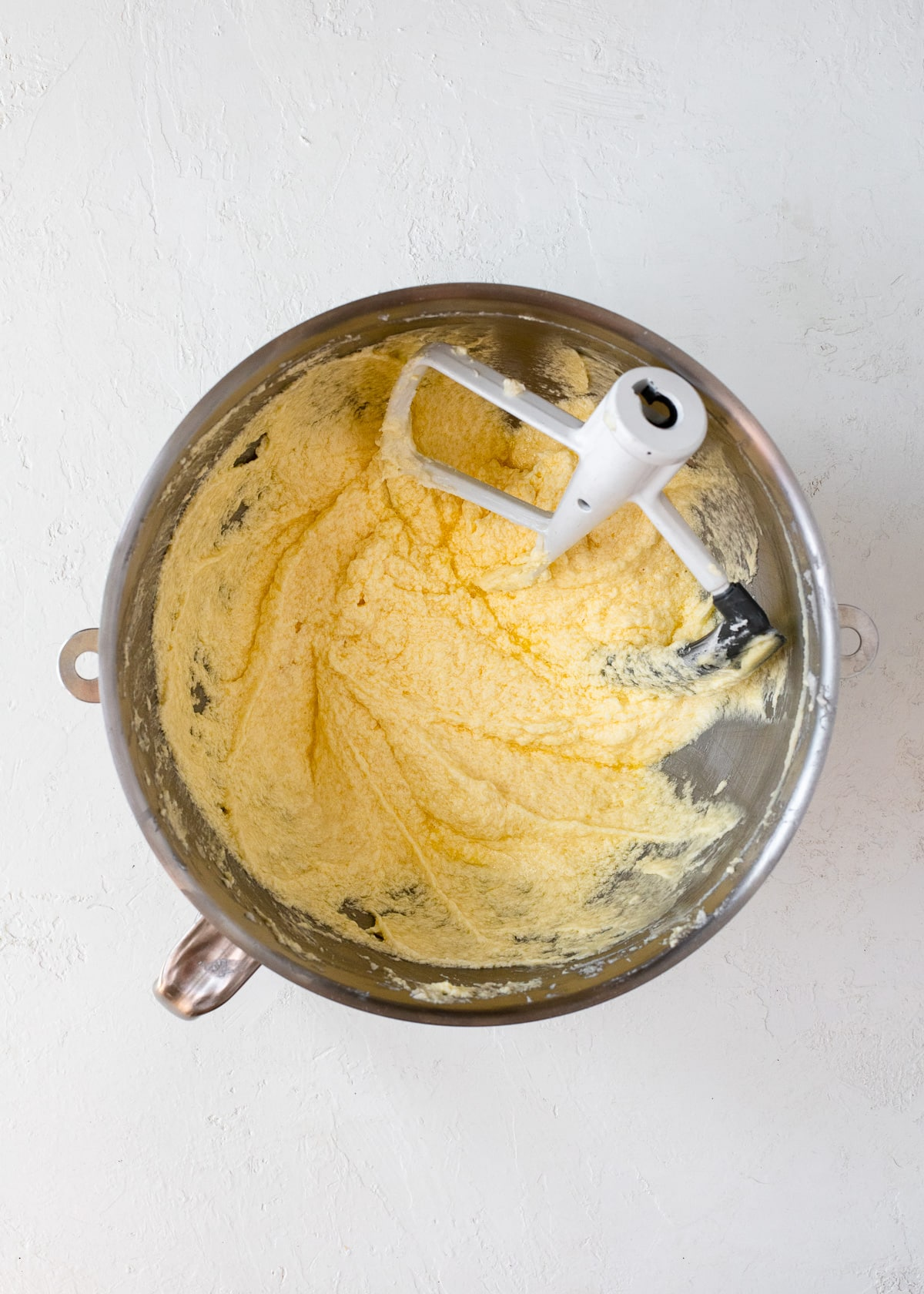 Overhead view of eggs being beaten into butter and sugar in a mixing bowl.