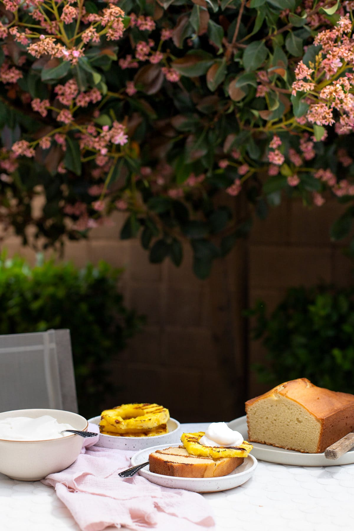 Pound cake being served with pineapple slices and whipped cream on a patio table.