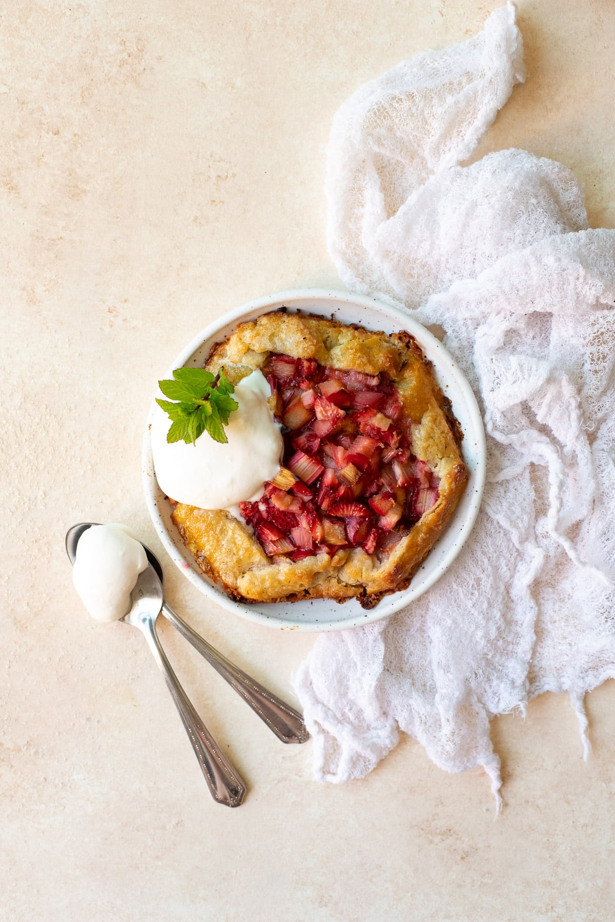 Overhead view of a single galette on a plate, topped with whipped cream and garnished with mint.