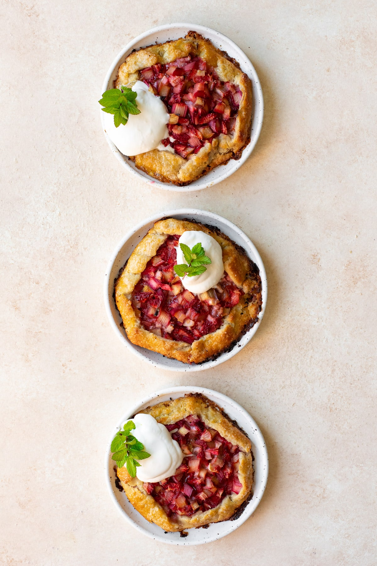 Overhead view of these mini galettes on small plates, topped with whipped cream and garnished with mint.