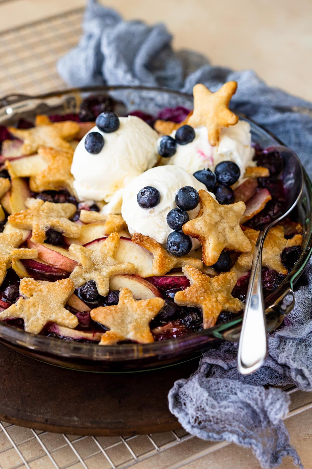 Spoon digging into a cobbler topped with pie crust stars and vanilla ice cream.