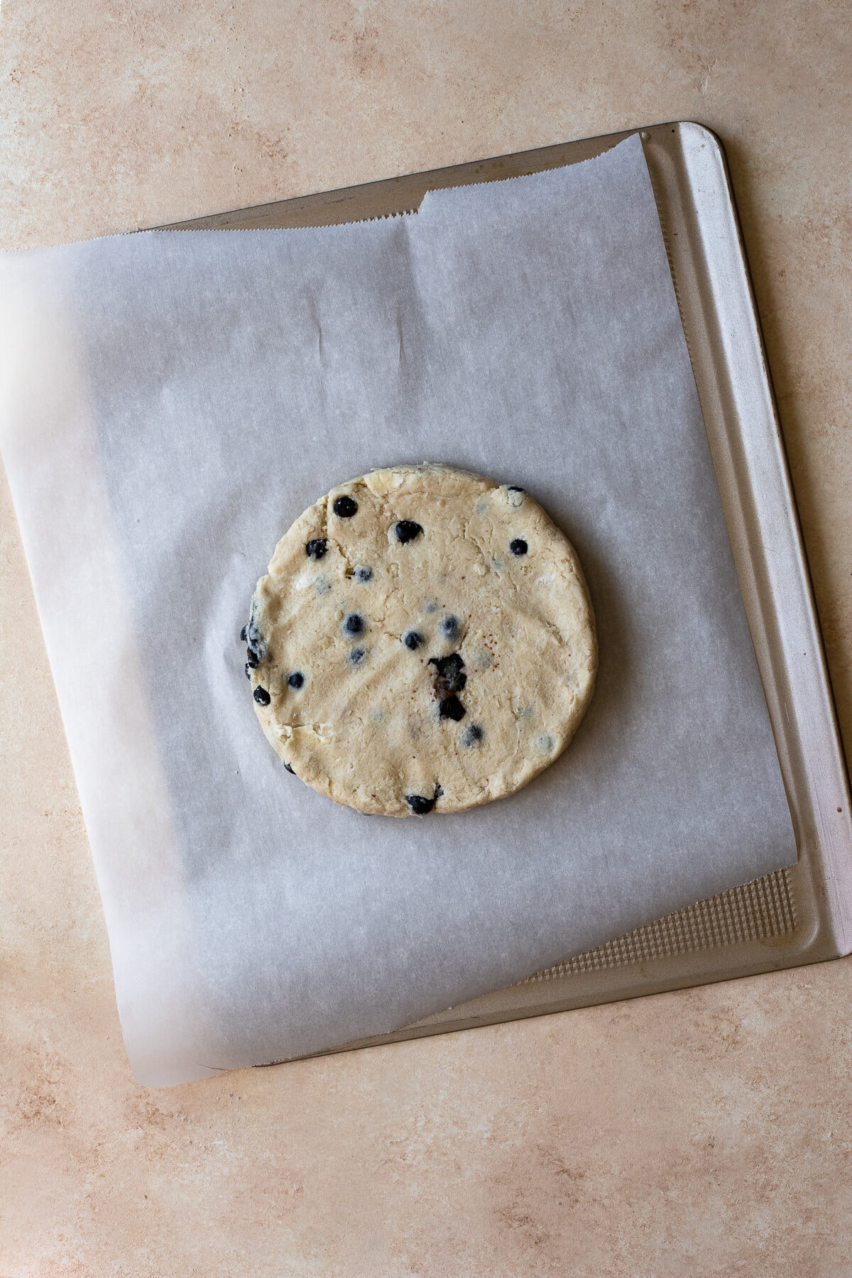 Scone dough flattened into a disc on a parchment-lined baking sheet.