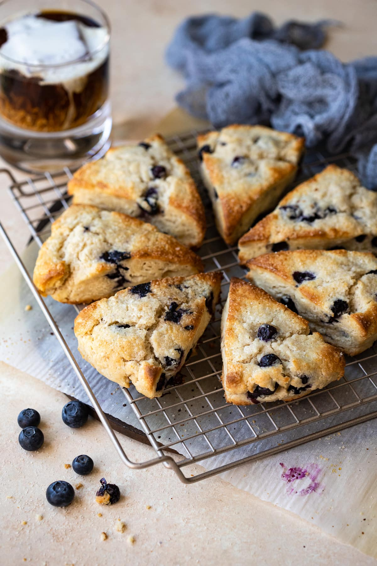 Blueberry scones on a wire rack, with iced coffee in the background.
