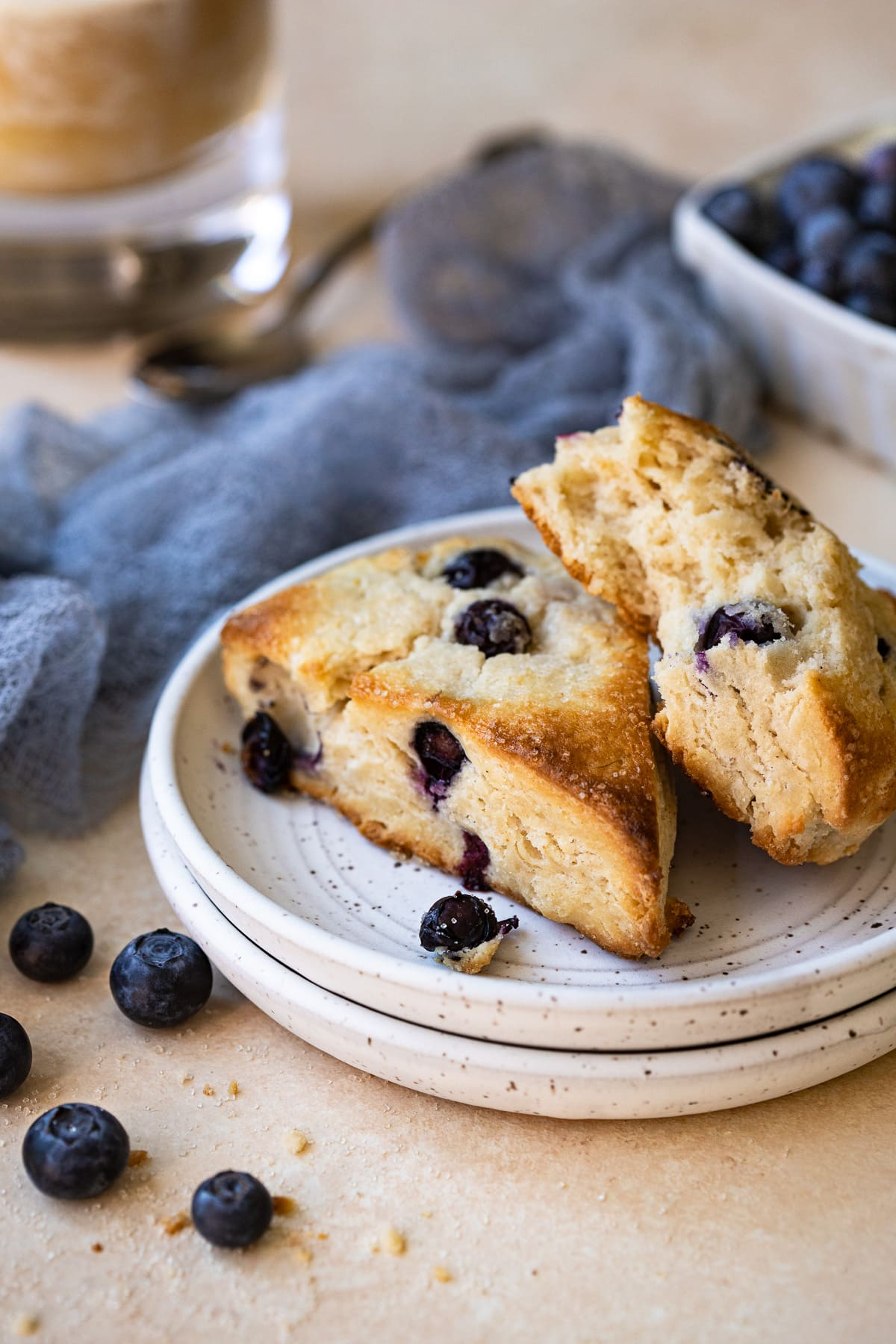 Two blueberry scones on stacked plates, with iced coffee in the background.