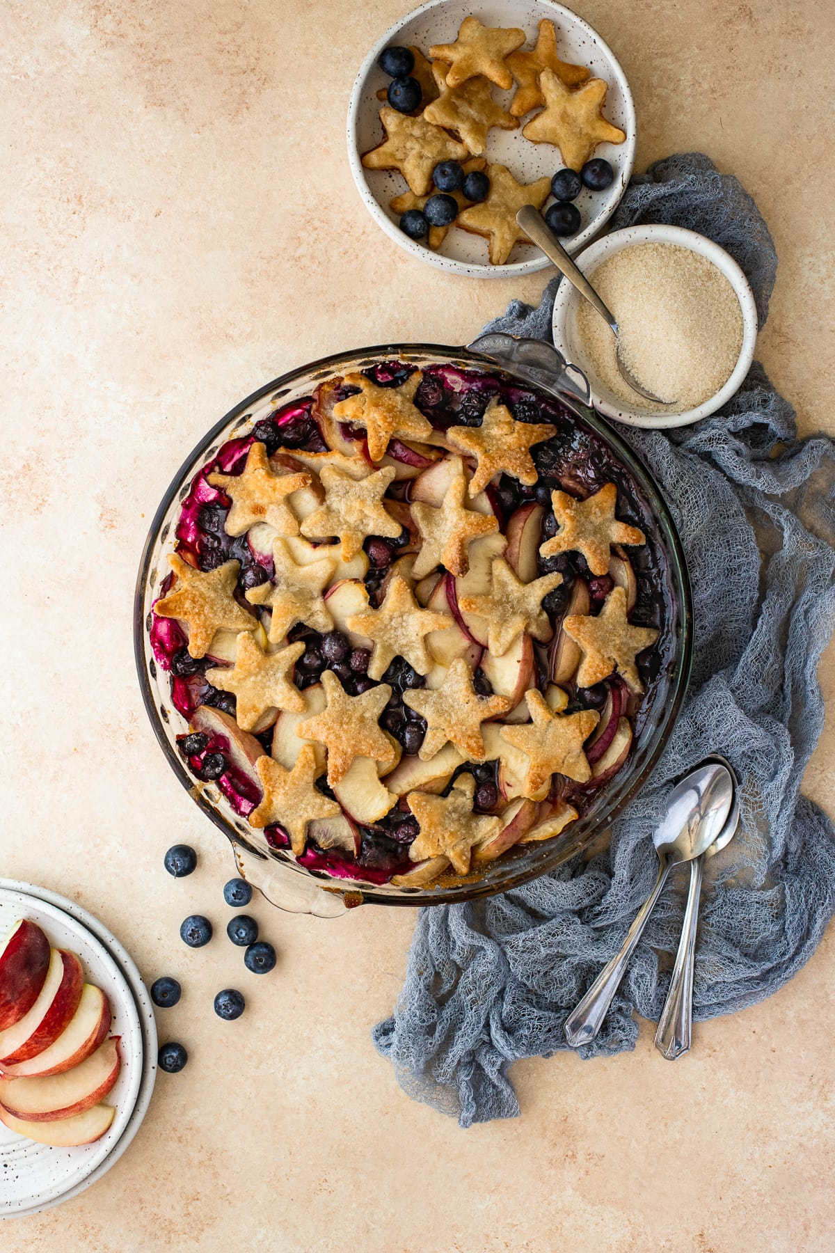 Cobbler baked in a pie dish, topped with pie crust stars, surrounded by fruit.
