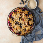 Cobbler topped with pie crust stars, baked in a pie dish.
