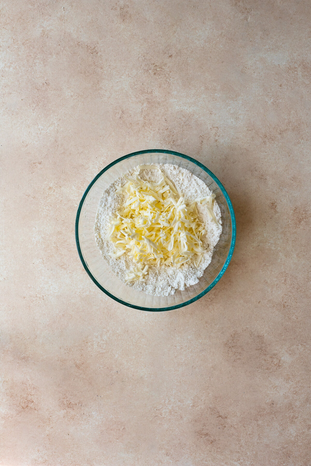 Grated butter added to a bowl of dry ingredients.
