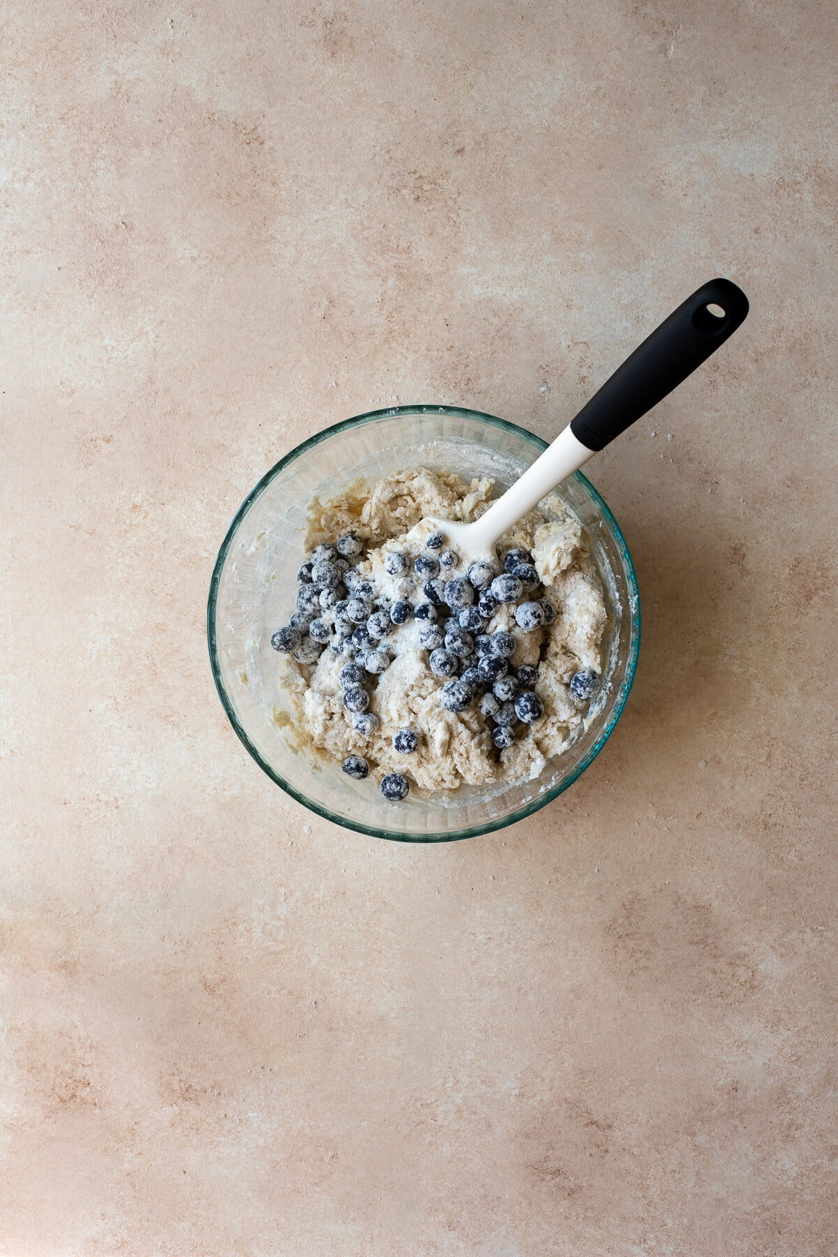 Blueberries being folded into scone dough in a bowl.