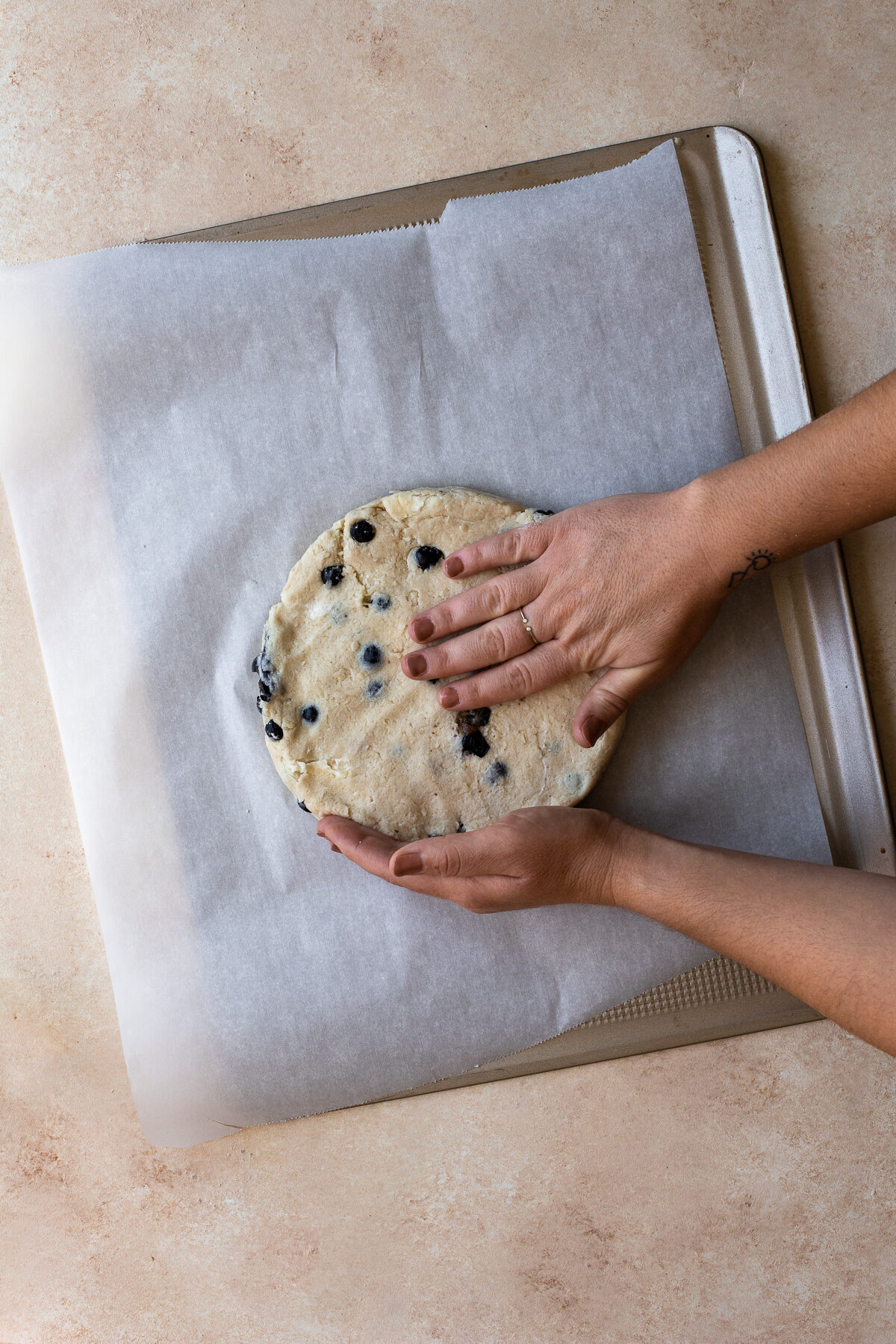 Scone dough being patted into a disc on a baking sheet.