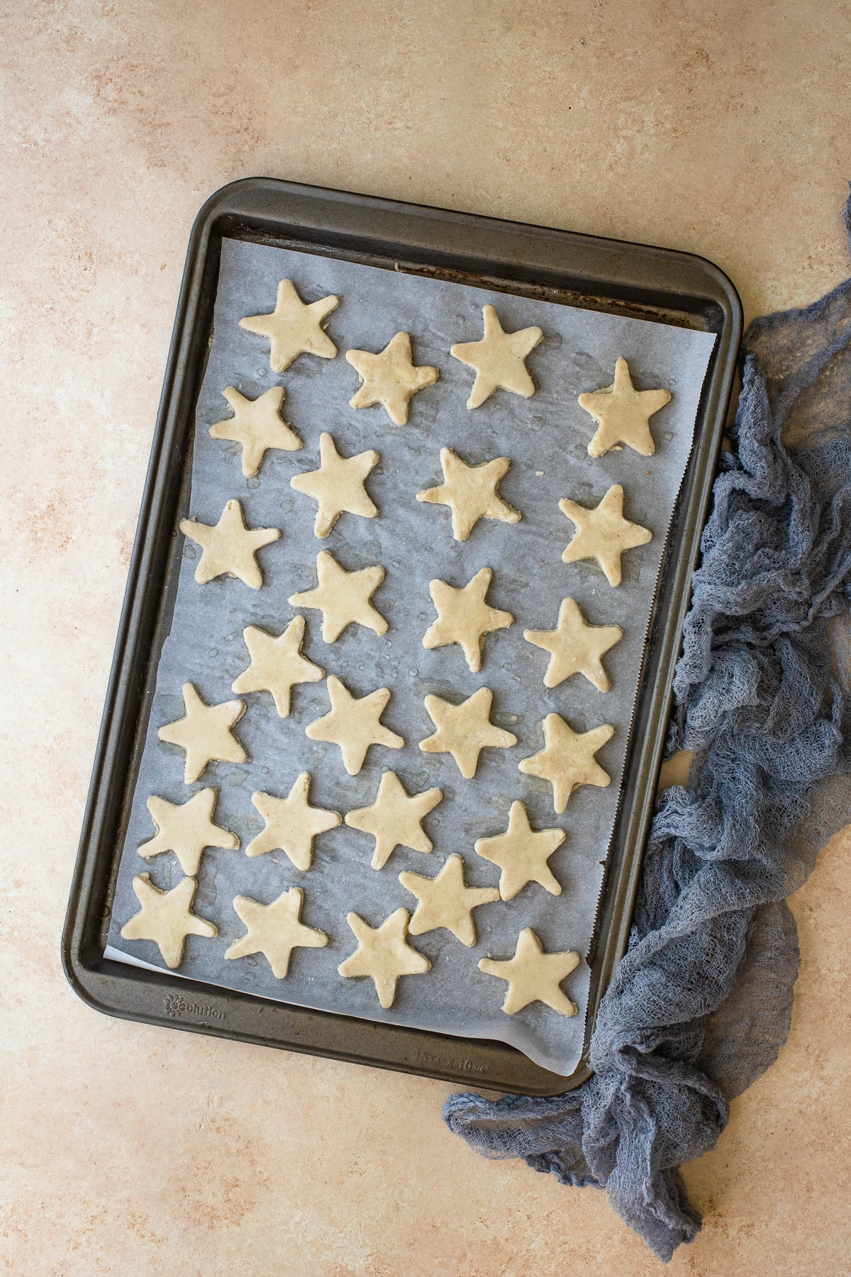 Pie crust stars brushed with egg wash on a parchment-lined baking sheet.