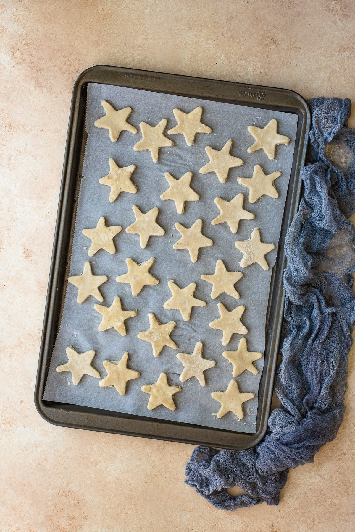 Pie crust stars arranged on a parchment-lined baking sheet.