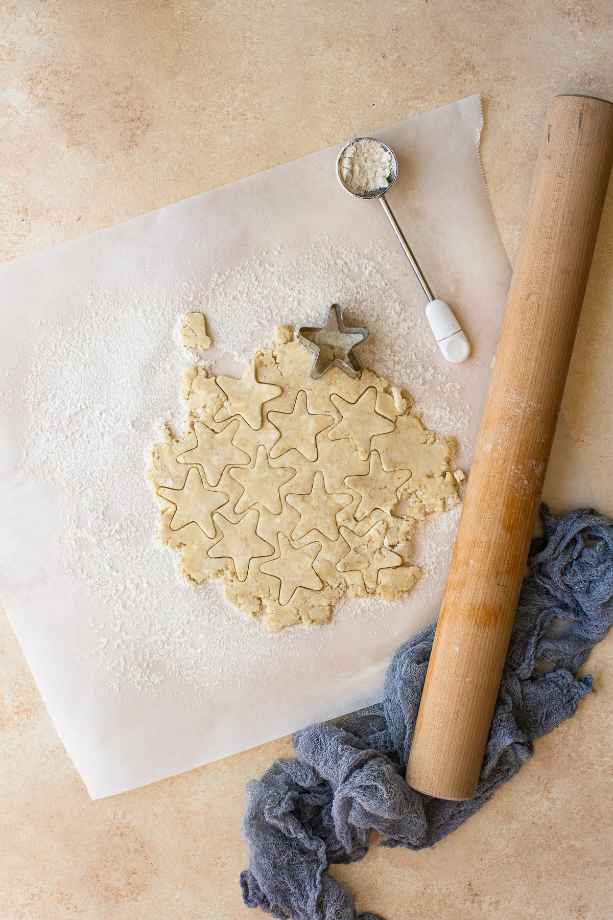 Pie crust dough being rolled out and cut into stars.