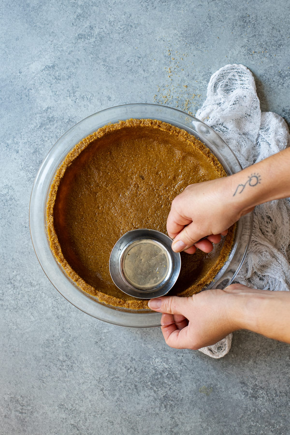 Pressing graham cracker crust into a pie dish with the bottom of a measuring cup.