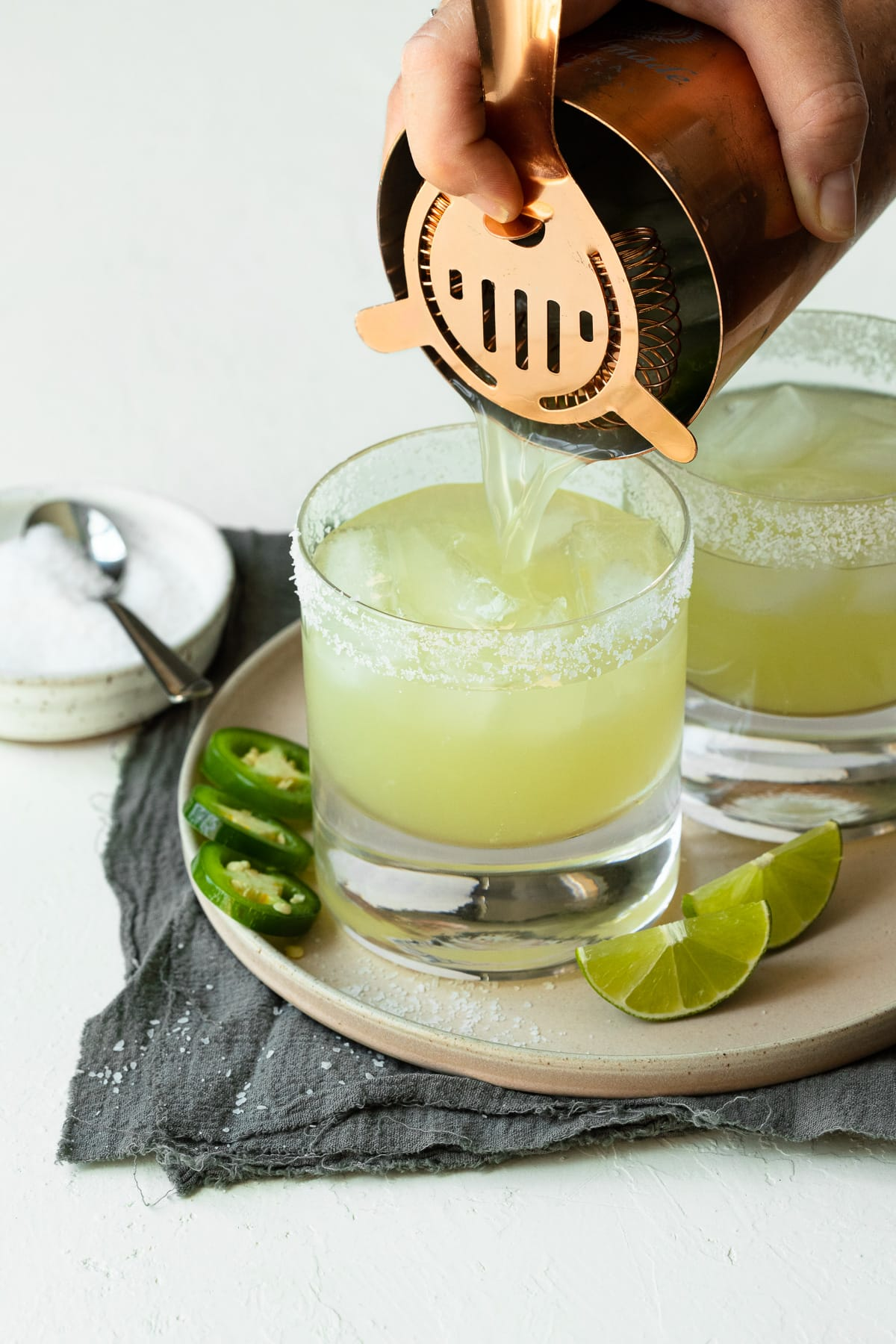 Margarita being poured into a lowball glass over ice.