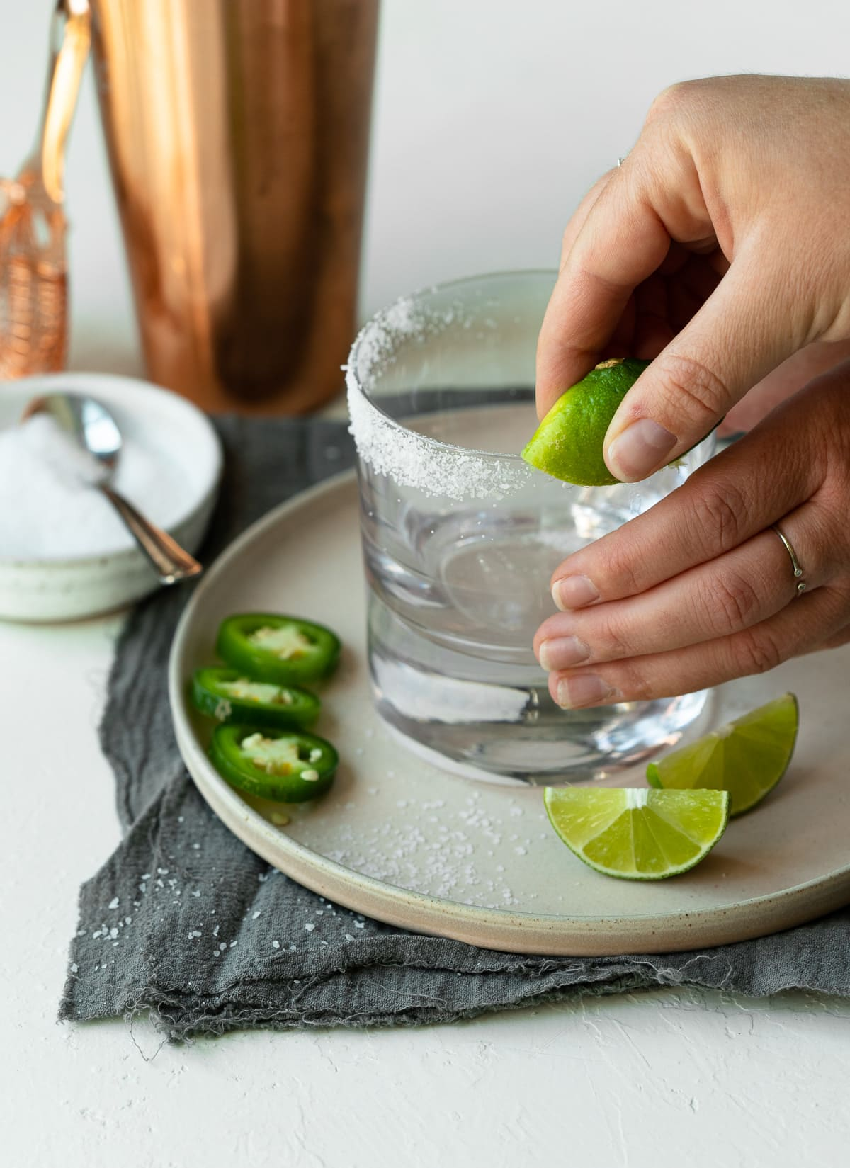 Lowball glass being prepped with lime and salt rim.