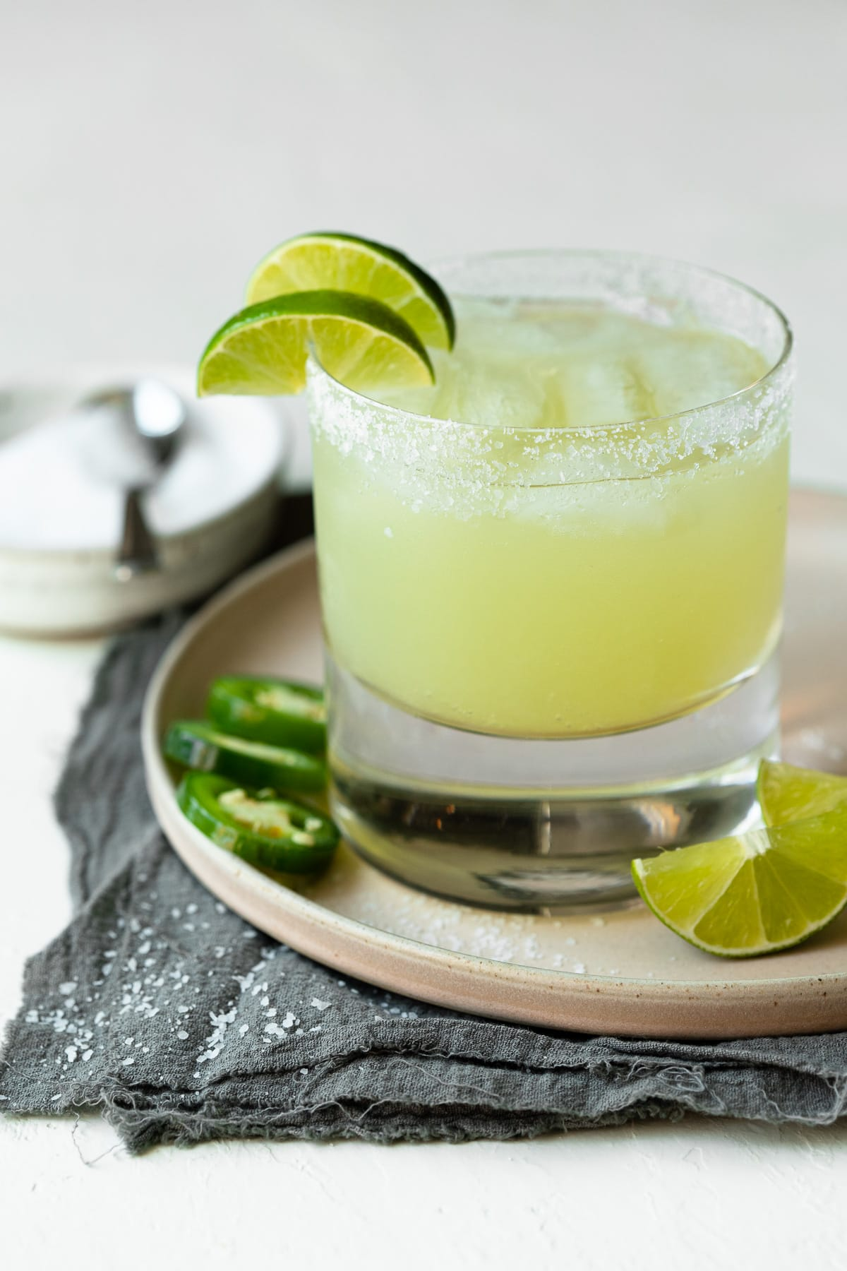 Margarita on the rocks with a salt rim and lime garnish.