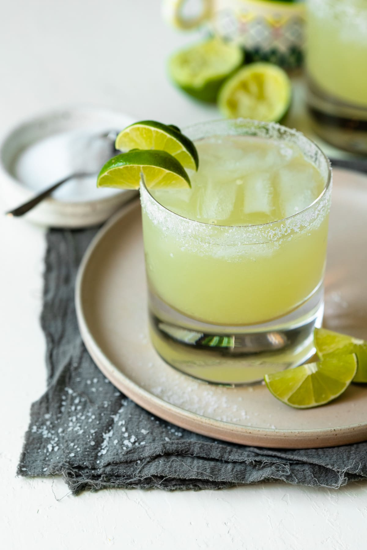 Two margaritas in lowball glasses, one garnished with lime wedges.