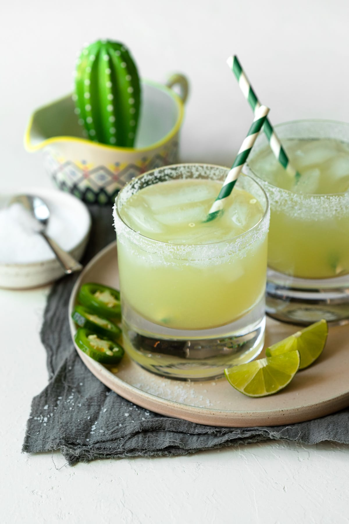 Two margaritas on the rocks, with striped straws.