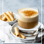 Coffee in a glass topped with cinnamon, served with rolled cookies, with text overlay.