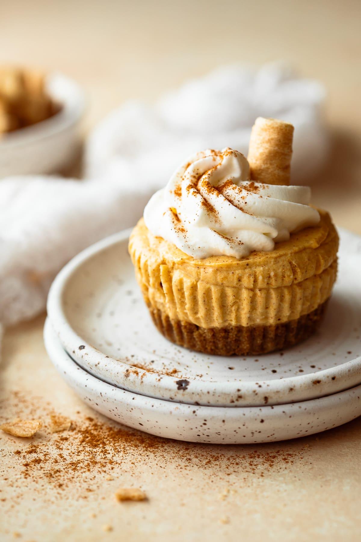 Mini pumpkin spice cheesecake on stacked white plates.